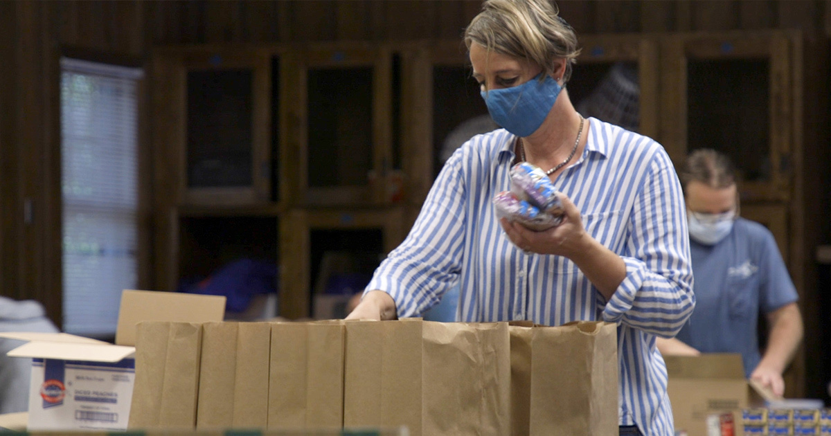 A woman stands over brown bags, filling them with food. She has her blue mask on to protect others around her from the spread of Covid-19.