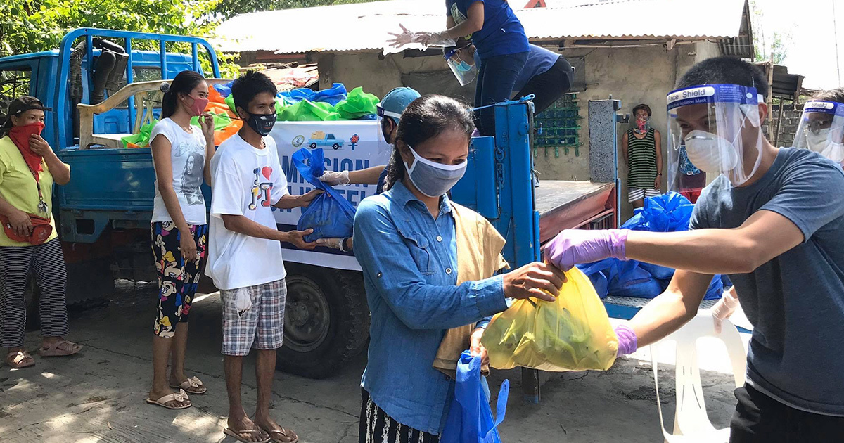 A woman receives a yellow bag of food as a part of UMCOR's Covid-19 response. She, and others around her, are wearing masks. Those delivering food stand in truck beds.